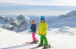 Szczęśliwi dzieci cieszy się zimę być na wakacjach w górach Zdjęcie Stock