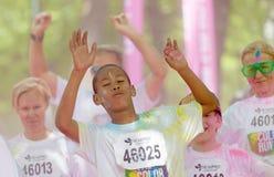 Szczęśliwi dzieci i dorosli z menchiami barwią pył w ich twarzy i Obrazy Royalty Free