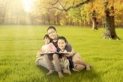 Szczęśliwi dzieci i ojca obsiadanie przy jesień parkiem Obraz Stock