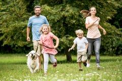 Szczęśliwi dzieci i rodzice z psem obraz stock