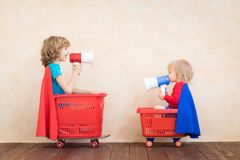 Szczęśliwi dzieci jedzie zabawkarskiego samochód w domu obraz stock