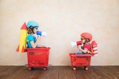 Szczęśliwi dzieci jedzie zabawkarskiego samochód w domu obrazy royalty free