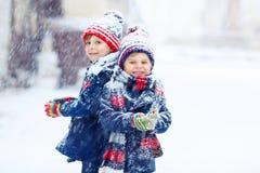 Szczęśliwi dzieci ma zabawę z śniegiem w zimie obrazy royalty free