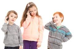 Szczęśliwi dzieci opowiada na telefonach komórkowych obrazy royalty free