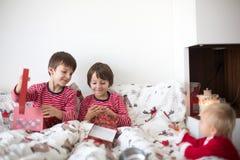 Szczęśliwi dzieci, otwiera boże narodzenie teraźniejszość w łóżku zdjęcie royalty free