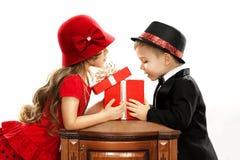 Szczęśliwi dzieci otwiera prezent Obrazy Royalty Free
