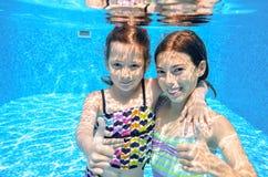 Szczęśliwi dzieci pływają w basenie podwodnym, dziewczyn pływać Zdjęcie Royalty Free