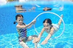 Szczęśliwi dzieci pływają w basenie podwodnym, dziewczyn pływać Fotografia Stock