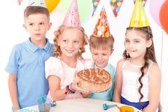 Szczęśliwi dzieci pozuje z urodzinowym tortem fotografia stock
