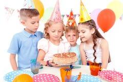Szczęśliwi dzieci pozuje z urodzinowym tortem Obrazy Royalty Free