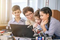 Szczęśliwi dzieci uczą się programowanie używać laptopy na extracurricular klasach fotografia royalty free