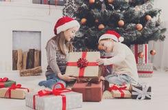 Szczęśliwi dzieci w Santa kapeluszach odwija boże narodzenie teraźniejszość obraz royalty free