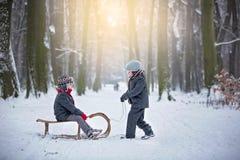 Szczęśliwi dzieci w zima parku, bawić się wraz z saneczki obrazy stock