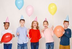 Szczęśliwi dzieci z colourful balonami nad ścianą fotografia royalty free