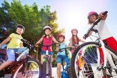 Szczęśliwi dzieci z ich bicyklami w lato parku Obrazy Stock
