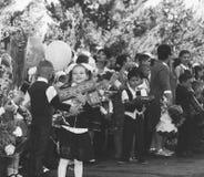Szczęśliwi dzieci zapisujący się w pierwszej klasie z prezentami w rękach nauczyciele i szkoła średnia ucznie na uczą kogoś linię Zdjęcie Royalty Free
