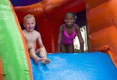 Szczęśliwi dzieciaki ślizga się w dół nadmuchiwanego odbicie dom Zdjęcia Royalty Free