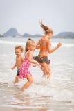 Szczęśliwi dzieciaki bawić się na plaży obraz stock