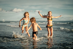 Szczęśliwi dzieciaki bawić się na plaży zdjęcia royalty free