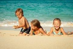 Szczęśliwi dzieciaki bawić się na plaży fotografia royalty free