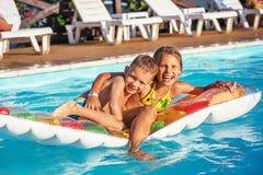 Szczęśliwi dzieciaki bawić się w błękitne wody pływacki basen Zdjęcie Stock