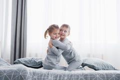 Szczęśliwi dzieciaki bawić się w białej sypialni Chłopiec, dziewczyna, brat i siostra jest ubranym piżamy, bawić się na łóżku szk Zdjęcia Stock