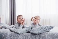Szczęśliwi dzieciaki bawić się w białej sypialni Chłopiec, dziewczyna, brat i siostra jest ubranym piżamy, bawić się na łóżku szk Zdjęcia Royalty Free