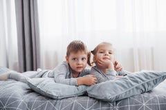Szczęśliwi dzieciaki bawić się w białej sypialni Chłopiec, dziewczyna, brat i siostra jest ubranym piżamy, bawić się na łóżku szk Obraz Royalty Free