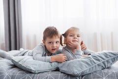 Szczęśliwi dzieciaki bawić się w białej sypialni Chłopiec, dziewczyna, brat i siostra jest ubranym piżamy, bawić się na łóżku szk Fotografia Royalty Free