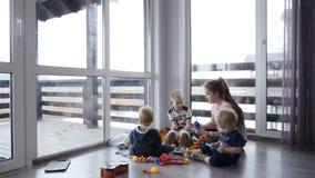Szczęśliwi dzieciaki bawić się wpólnie Dziecka pojęcie Dzieci siedzi na podłoga w intymnym domu z panoramicznymi okno i zbiory wideo