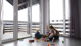 Szczęśliwi dzieciaki bawić się wpólnie Dziecka pojęcie Dzieci siedzi na podłoga w intymnym domu z panoramicznymi okno i zbiory
