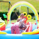 Szczęśliwi dzieciaki bryzga w nadmuchiwanym ogrodowym basenie obrazy royalty free