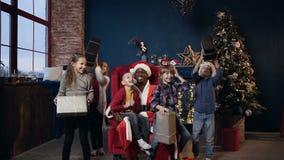 Szczęśliwi dzieciaki joying prezenty dostaje od Święty Mikołaj, rzuca w górę i ono uśmiecha się na choinki tle, zdjęcie wideo