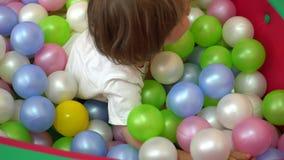 Szczęśliwi dzieciaki ono uśmiecha się i bawić się w wielo- coloured balowym basenie preschool zbiory wideo