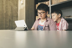Szczęśliwi dzieciaki patrzeje pastylka komputer Obrazy Royalty Free