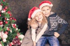 Szczęśliwi dzieciaki przy Bożenarodzeniową wakacyjną pobliską dekorującą choinką zdjęcia royalty free