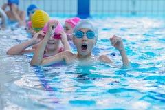 Szczęśliwi dzieciaki przy pływackim basenem Młoda i pomyślna pływaczki poza fotografia royalty free