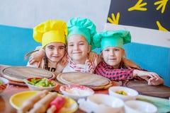 Szczęśliwi dzieciaki przy pizzy kucharstwem zdjęcie royalty free