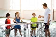 Szczęśliwi dzieciaki uczy się reguły tenisowa gra Obraz Royalty Free