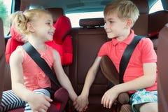 Szczęśliwi dzieciaki, urocza dziewczyna z jej bratem siedzi wpólnie w m Obraz Stock