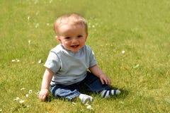 Szczęśliwi dziesięć miesiąc starej chłopiec siedzących puszków outdoors Obraz Stock