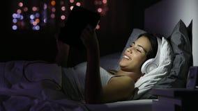 Szczęśliwi dziewczyny dopatrywania wideo w pastylce w nocy zbiory