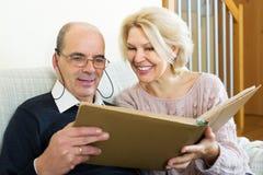 Szczęśliwi emeryci ogląda starych photoes obraz stock