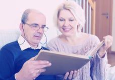 Szczęśliwi emeryci ogląda starych photoes Zdjęcie Stock