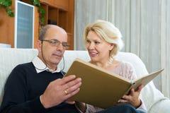 Szczęśliwi emeryci ogląda starych photoes obrazy stock