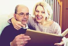 Szczęśliwi emeryci ogląda starych photoes zdjęcie royalty free
