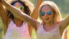 Szczęśliwi faceci i dziewczyny dźwigania ręki, doskakiwanie, wiszący przy Holi przyjęciem out outdoors zbiory wideo