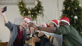Szczęśliwi faceci i dziewczyny trzyma szkła wino kapelusze robią selfie fotografii na smartphone blisko ubierali w Święty Mikołaj zbiory wideo