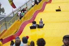 Szczęśliwi fairgoers jadą Gigantycznego obruszenie przy Minnestoa stanu jarmarkiem Obrazy Royalty Free