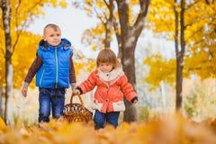 Szczęśliwi figlarnie dzieci w jesień parku Obrazy Royalty Free